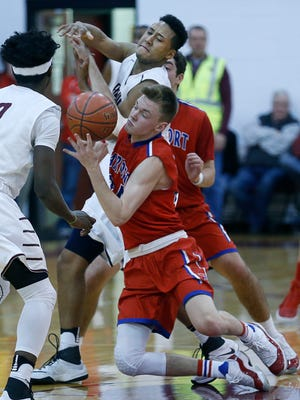 Fairport's TJ Hendricks and Aquinas' Graycen Carter look to take possession of a loose ball in the second quarter at Aquinas Institute.