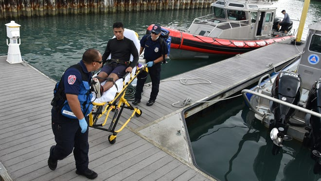 Guam Fire Department personnel prepare to take an 18-year-old man to Guam Memorial Hospital from the Hagatna marina on Saturday, Aug. 8. The teen was able to walk from the GFD rescue boat to the gurney. He and another rescued swimmer were in stable condition at hospitals by the afternoon, authorities said.