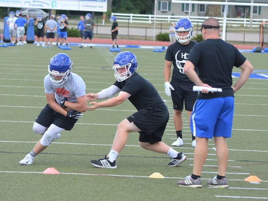 Harper Creek quarterback Sam Bussler hands the ball off during a drill while being watched by first-year head coach Mason Converse.