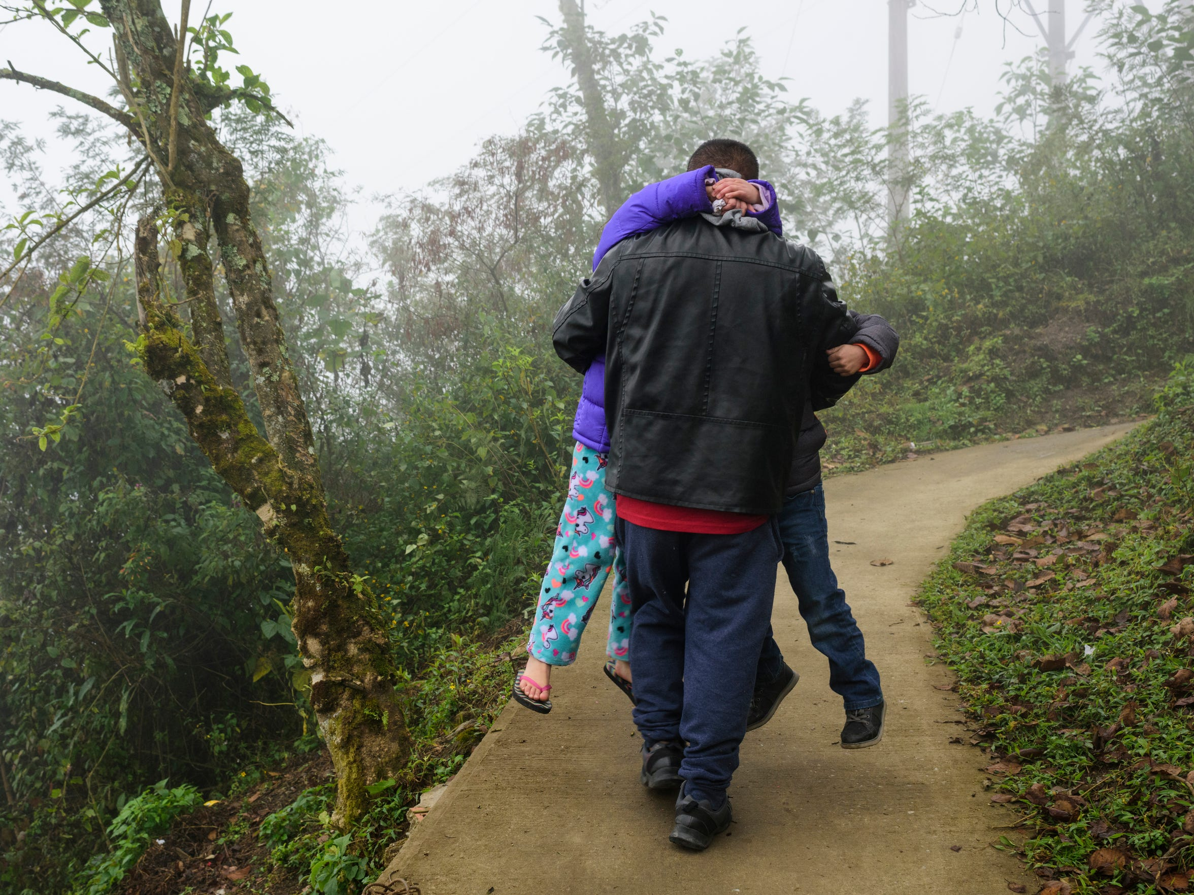 Antonio Cuahua carries his two youngest children Marrissiah Cuahua, 6, and Enrique Cuahua, 5, up the pathway that connects their home to their extended family's house on Jan. 12 in rural Atlanca, a town located about an hour away from Orizaba, Mexico.