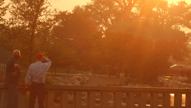 Two men admire an orange sunset in downtown Reno on Sept. 15, 2014. The smoke from the King Fire in El Dorado County, which covered the city, created an orange glow during sunset.