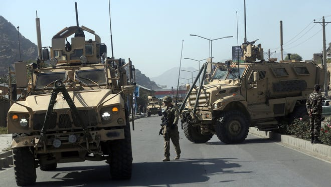 A U.S. soldier directs his colleague at the site a bomb attack that targeted several armored vehicles belonging to forces attached to the NATO Resolute Support Mission, in downtown of Kabul, Afghanistan, Sunday, Oct. 11, 2015.