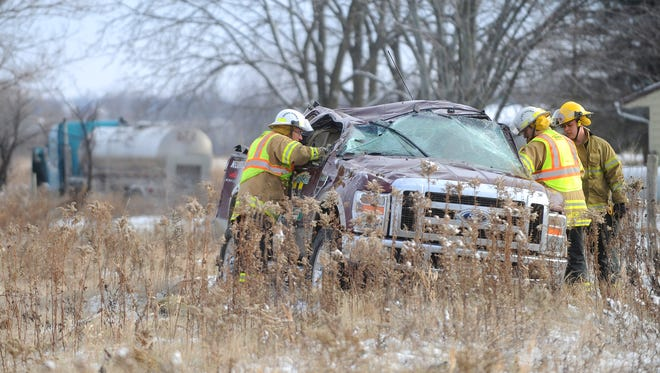 Town of Fond du Lac firefighters inspect a pick up truck involved in a rollover crash Wednesday morning,  Nov. 19, 2014, on 151, just south of Military Road/Highway D interchange. A tanker truck, also involved, is seen in the background.