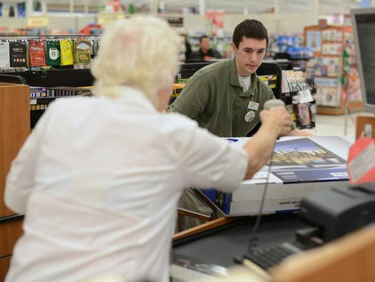 Shopko employee Nathan Buergi lifts up a television