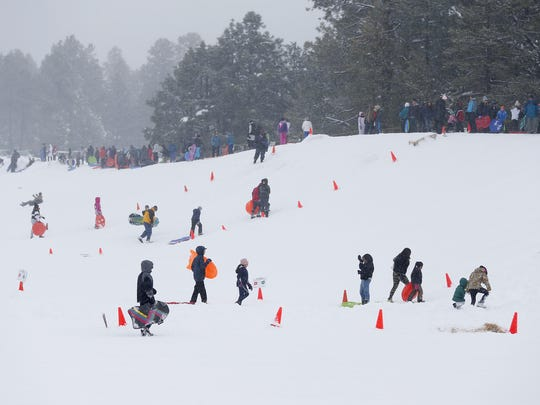 Sledders play on a hill at at Wing Mountain Snow Play Area north of Flagstaff January 22, 2017.
