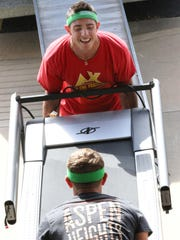 Bellhops' Jade Pavia, top, and Allen Bates load a very heavy treadmill onto a truck at an apartment in Brookline on Sept. 19.