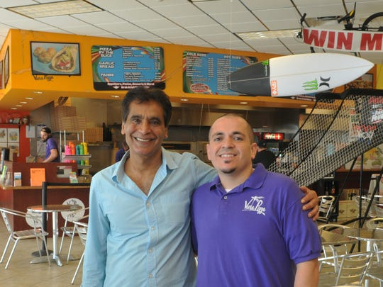 Mike Acosta, right, owner of Viera Pizza, with Naweed Akram, owner of the Stadium Mobil station, where Acosta's business is located.