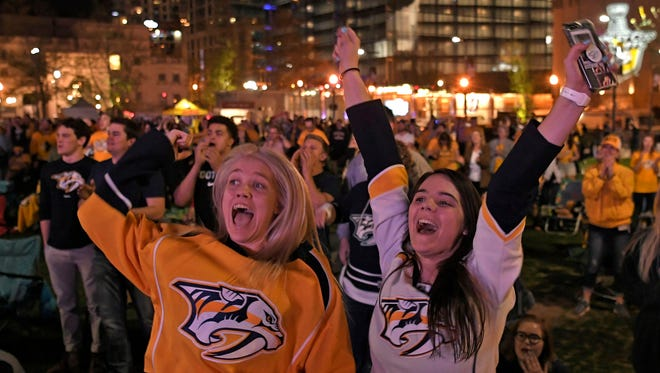 Predators fans Mackenzie Giunn and Lilly Nota celebrate after the third period in game 1 of the first round NHL Stanley Cup Playoffs at the Bridgestone Arena Thursday, April 12, 2018, in Nashville, Tenn.