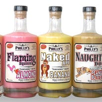 """Phil Orlenko, founder of Philly's Premium Beverages, with the model for his Naughty Dog Peanut Butter Egg Crème Liqueur. Wilbur is a rescue dog from a nearby shelter who also provides """"security"""" at company headquarters in Grafton."""