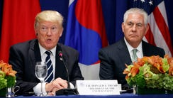 Secretary of State Rex Tillerson looks on as President