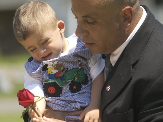Robert Alonso of Stony Point and his son, Robbie, 2, place flowers on the casket of his wife, Janet, after a service at Mount Repose Cemetery in Haverstraw Saturday. Janet Alonso was killed in the Sept. 11 attacks on the World Trade Center.
