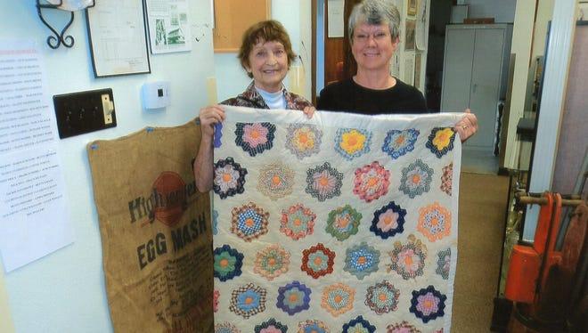 Joyce Wilson (left) and Linda Gardner holding a Shellenberger quilt.