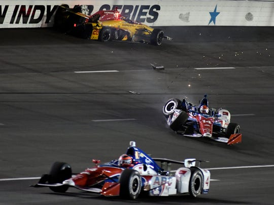 Ryan Hunter-Reay, top, and Carlos Munoz (14) wreck in Turn 3 as Conor Daly (4) drops down to avoid the accident during an IndyCar auto race at Texas Motor Speedway, Saturday, June 10, 2017, in Fort Worth, Texas. (AP Photo/Larry Papke)