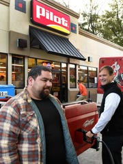 Knoxville City Council member Marshall Stair, right, pumps gas for Tom Mikell at the Pilot location at Broadway and Washington Pike to raise money for United Way on Oct. 11, 2016.