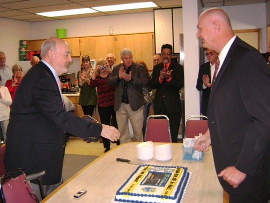 Joe Magill, right, shakes the hand of Mayor Tom before cutting the cake baked for a reception marking his retirement as police chief.