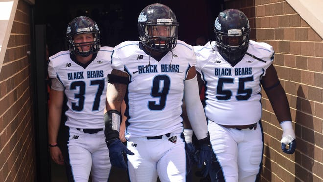 Sep 5, 2015; Boston, MA, USA; Maine Black Bears place kicker Sean Decloux (37), defensive end Trevor Bates (9), and offensive lineman Bruce Johnson (55) walk onto the field prior to their game against the Boston College Eagles at Alumni Stadium.