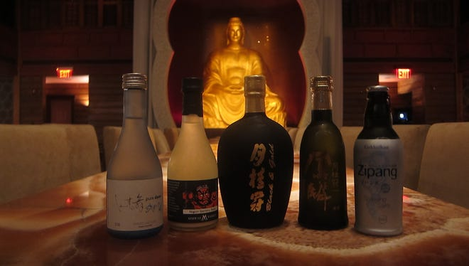 A row of sake bottles stand before a statue of Buddha at Buddakan in Atlantic City.