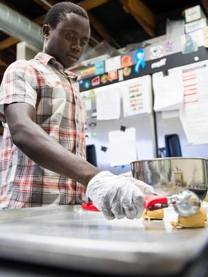 Pascal Masumbuko, an African refugee, puts dough on a tray to make cookies at The Refuge cafe in Phoenix, AZ, on Friday, June 26, 2015. The restaurant teaches refugees and at-risk youth about work.