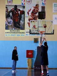 In this Friday, Feb. 17, 2017, photo in Athens, Greece, Takis Zivas, left, coach of Filathlitikos, where Giannis Antetokounmpo had his first professional contract, gives directions to Panagiotis Stavrou, a 14-year-old basketball player. From a scrawny, literally hungry kid kicking a ball around in an open field in the Athens neighborhood of Sepolia to a starter in the NBA All-Star Game, Antetonkoumpo has come a very long way. (AP Photo/Thanassis Stavrakis)