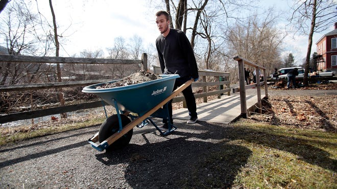 A volunteer transports leaves and brush off the trail during the Housatonic River Walk cleanup for the annual Earth Day Workday on April 19, 2014, in Great Barrington, Mass.