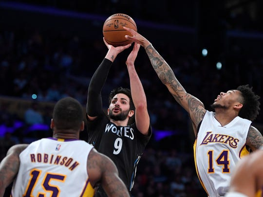 Minnesota Timberwolves guard Ricky Rubio, center, of Spain, shoots as Los Angeles Lakers forward Thomas Robinson and forward Brandon Ingram defend during the first half of an NBA basketball game, Sunday, April 9, 2017, in Los Angeles. (AP Photo/Mark J. Terrill)