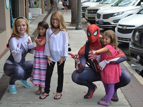 Spider-Man fans pose with cosplayers Lauren Edinger