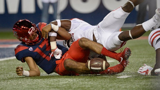 Wildcats quarterback Brandon Dawkins (13) loses the ball as he is tackled by Houston Cougars safety Garrett Davis. The Wildcats changed quarterbacks in the loss.