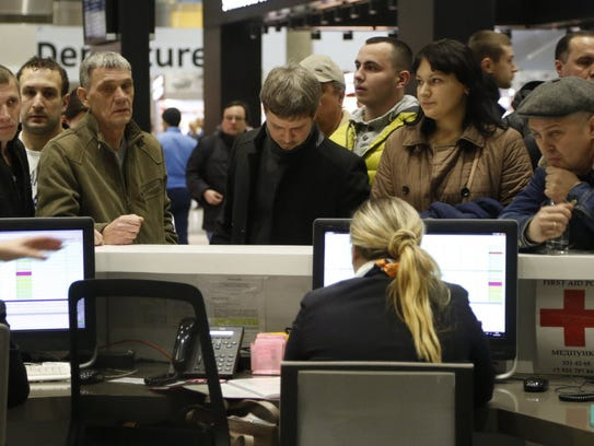 People gather at the airline information desk at the