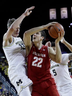Michigan's Moritz Wagner and D.J. Wilson converge on Wisconsin's Ethan Happ on Thursday night.