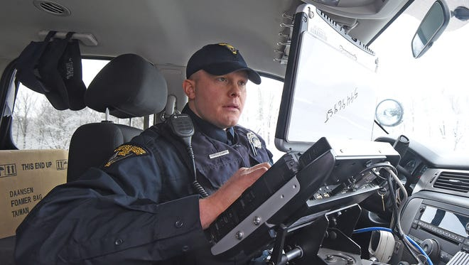 Officer Brian Wilson of the Ohio Highway Patrol Motor Carrier Enforcement works on his computer after making a stop on US 30 on Friday.