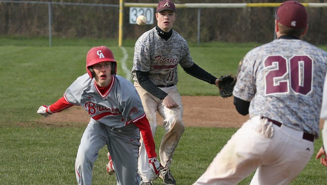 Canandaigua's Hayden Roeder, left, is caught in a rundown between Greece Arcadia's Dan Freese, center, and Kyle Bailey, right, as he attempts a suicide squeeze play in the fifth inning during their game Monday at Greece Arcadia High School.  Roeder was tagged out by Bailey as he tried to get back to third.  Arcadia won the game 3-1.