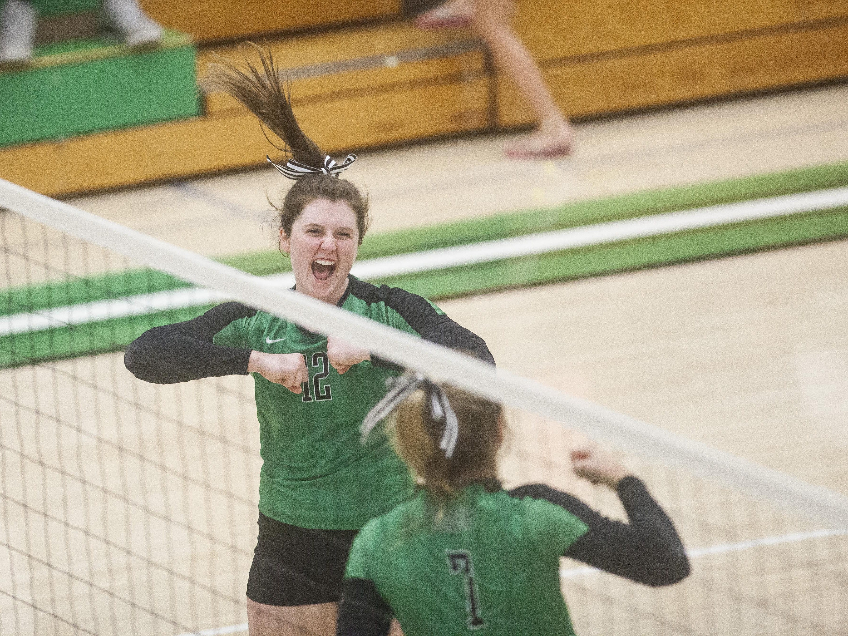 Mimi Arrington and Olivia Reed celebrate a Yorktown kill Monday evening during their match against Wapahani. The Tigers swept the Raiders.