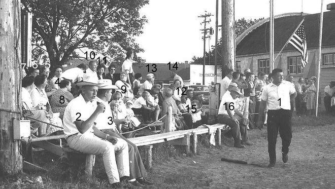 Rio Creek fans were there in July 1964 to cheer on their baseball team when it played Maplewood at the Forestville field next to Legion Hall. Food and beverage stands were adjacent to the hall, and Forestville Town Hall was the white building across the road. Rio Creek spectators are identified as follows: 1. Arnie Neuzil, 2. Jerry Neinas, 3. Leon Jacques, 4. Mildred Neuzil, 5. Marilyn Schneider, 6. Lorraine Neuzil, 7. Norma Teske, 8. Erma Villers, 9. Darlene Rhodes, 10. Al Breitlow, 11. Karen Breitlow, 12. June Kirchman, 13. Gerald Guth, 14. Fuzzy Kirchman. 15. Ervin Villers. 16. Roy Neuzil. But, who won the game?  The photo comes from the Heidmann Collection at the Algoma Public Library.