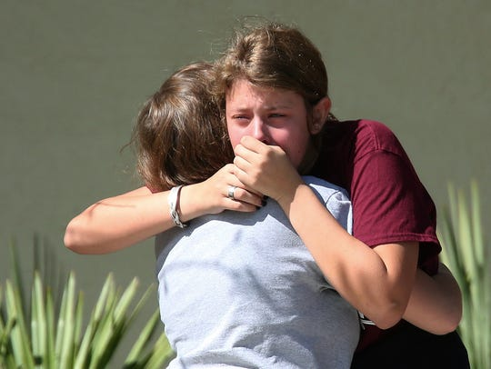 Students grieve outside Pines Trail Center where counselors