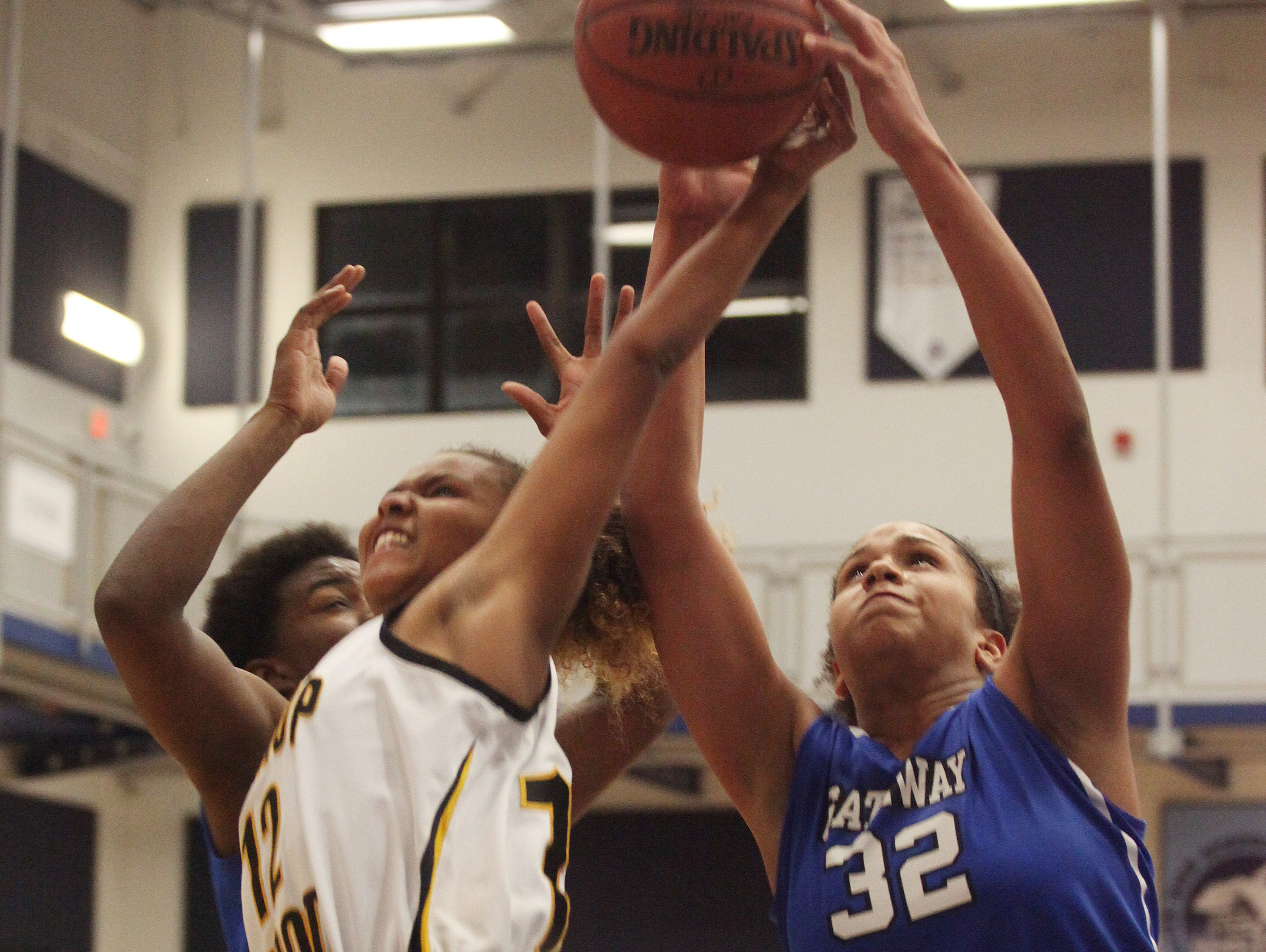 Gateway Charter's Tamia Battle and Bishop Verot's Sequoyah Robinson battle over the rebound during the District 4A-10 finals at Oasis High School on Thursday night.