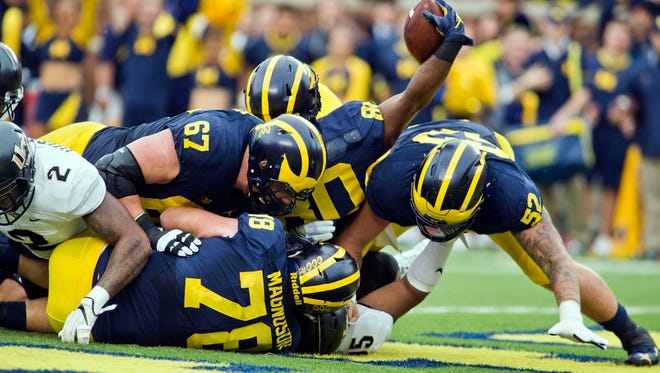 Michigan fullback Khalid Hill, center, rolls over teammates Kyle Kalis (67), Erik Magnuson (78), and Mason Cole (52), into the end zone for a touchdown in the first quarter against Central Florida at Michigan Stadium in Ann Arbor on Saturday, Sept. 10, 2016.