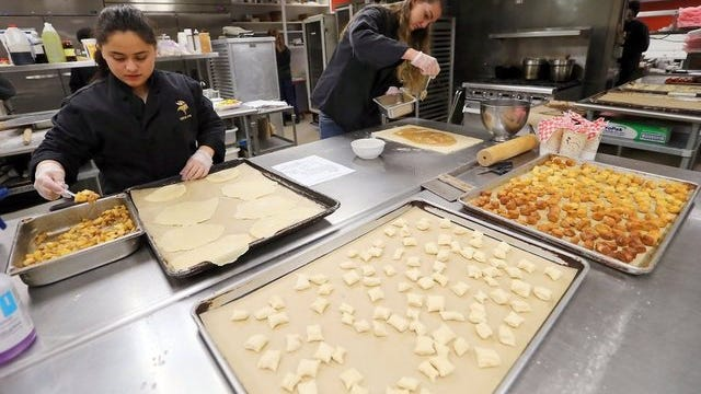 Cynthia Duran (left), 15, makes apple turnovers while fellow student Faith McConnoughey, 16, makes cinnamon rolls as part of the North Kitsap High School culinary arts program at the Odin Inn.   MEEGAN M. REID / KITSAP SUN
