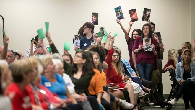 Alumni from Marjory Stoneman Douglas High School hold the photos of those killed in last week's shooting at a town hall for Congressman Francis Rooney on Thursday, Feb. 22, 2018, in Fort Myers.