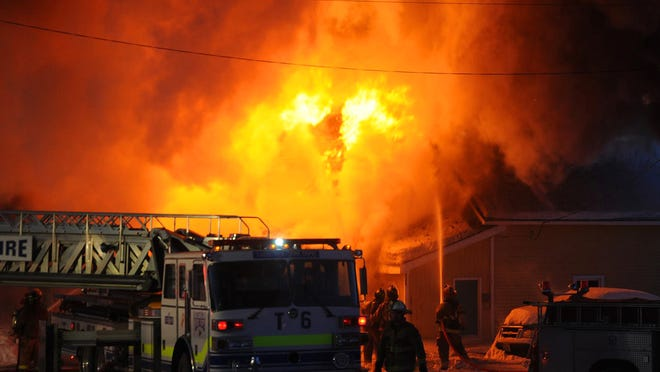 Flames burst from the roof of a the English Rose Inn on Vermont 242 in Westfield Friday.
