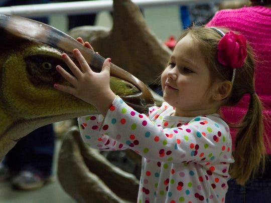 Olivia Lantrip, 3, makes friends with a dinosaur during the Jurassic Quest event at the Kentucky Convention Center Saturday afternoon. January 17, 2015.