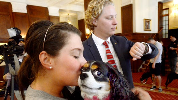 State Rep. Kevin Schreiber, D-York, is seen in this file photo with his wife, Jen, who is snuggling Lucy, their Cavalier King Charles spaniel, before a news conference at the Yorktowne Hotel on Aug. 29, 2013. Schreiber introduced legislation that would require pet shops to provide more information about dogs for sale. (Bill Kalina photo)