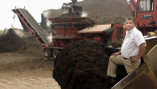In this file photo, Douglas Evans poses in front of a loader full of mulch at Evans Landscaping in Newtown.