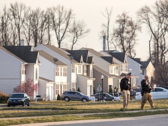 New Castle County police officers walk through a park looking for evidence after a shooting was reported at 105 Covington Place in New Castle on Wednesday afternoon.
