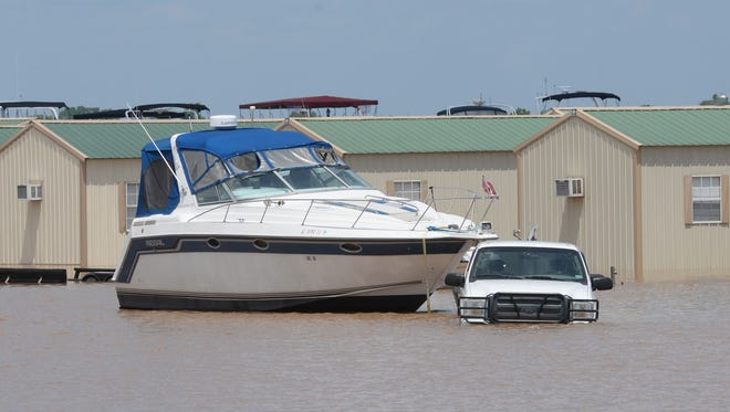 A stalled truck sits next to a boat in the parking lot of the Red River South Marina in Bossier Parish. Waters from the Red River have flooded the marina and gotten into several of the cabins and mobile homes there.