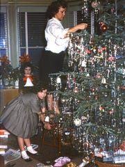 Gerry Wilson McConkey's mom, Dorothy Wilson, decorating their tree with Gerry's sister Cathy in 1961.