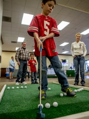 Ayden tries out his miniature golf skills with his brother, Gabe, as well as Big Brother Tom Headley and Big Sister Tina Headley. On Saturday, the boys attended the fourth annual Amateur Miniature Indoor Golf Outing, a fundraiser for the local chapter of the American Red Cross.