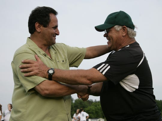 Former Williamston girls soccer coach Jim Flore, right,  greets DeWitt coach Jamal Mubarakeh during the Senior All-State game in 2012.