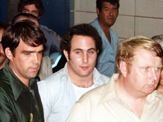 "Police officials surround David Berkowitz, 24, of Yonkers, N.Y., outside Brooklyn's 84th precinct after his arrest as the ""Son of Sam"" killer early Thursday, August 11, 1977."