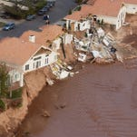 A row of damaged homes in the Riverwood subdivision cling to the banks of the Santa Clara River Thursday, Jan. 13, 2005 in St. George.
