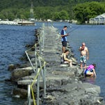 People fish and swim in Seneca Lake off the rocks at the public pier in Watkins Glen.